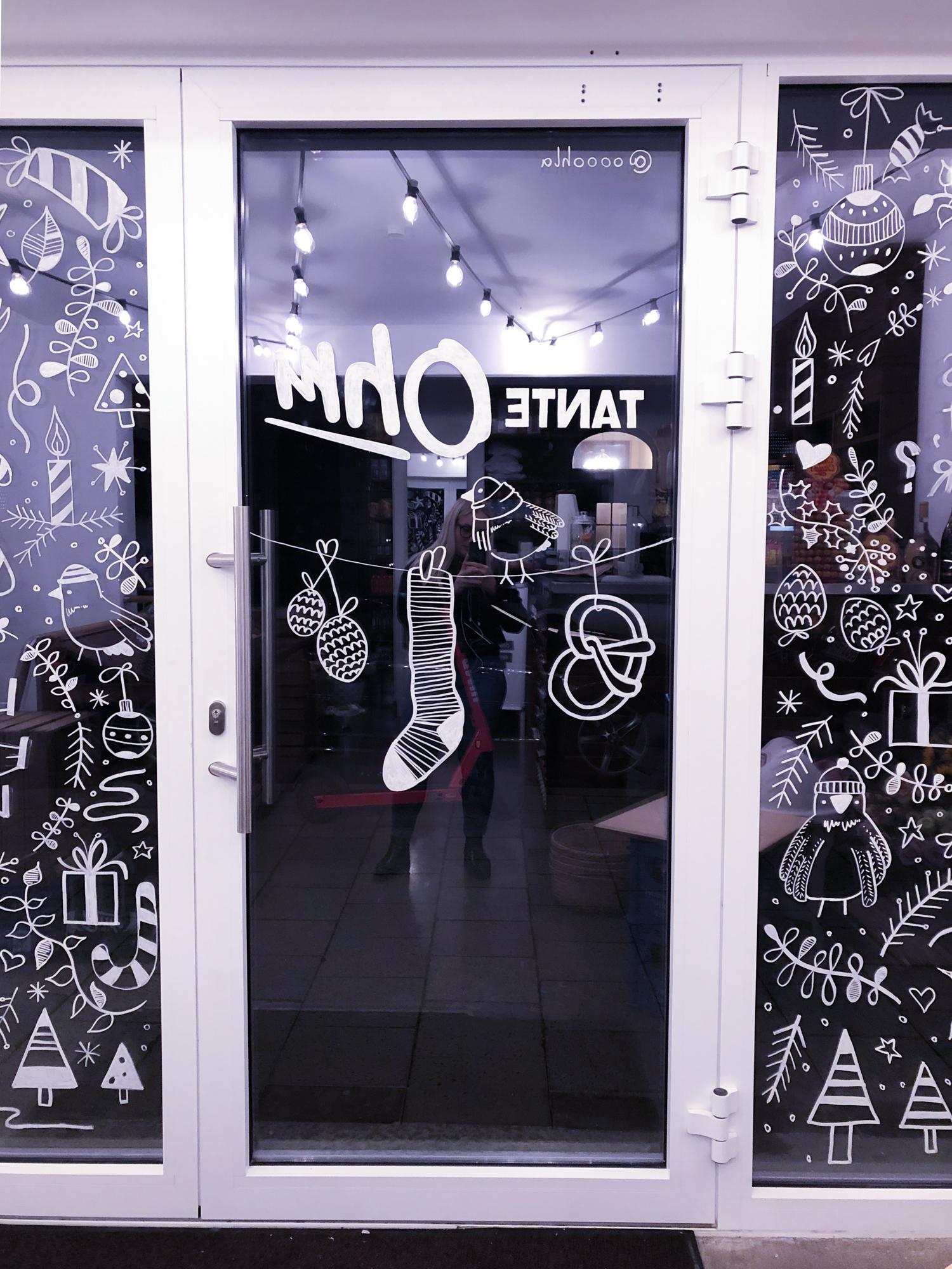 Auf der Eingangstür des Kiosks ist ein Vogel mit Schal auf einer Leine gemalt. An der Schnur hängen außerdem noch Tannenzapfen und eine Breze.