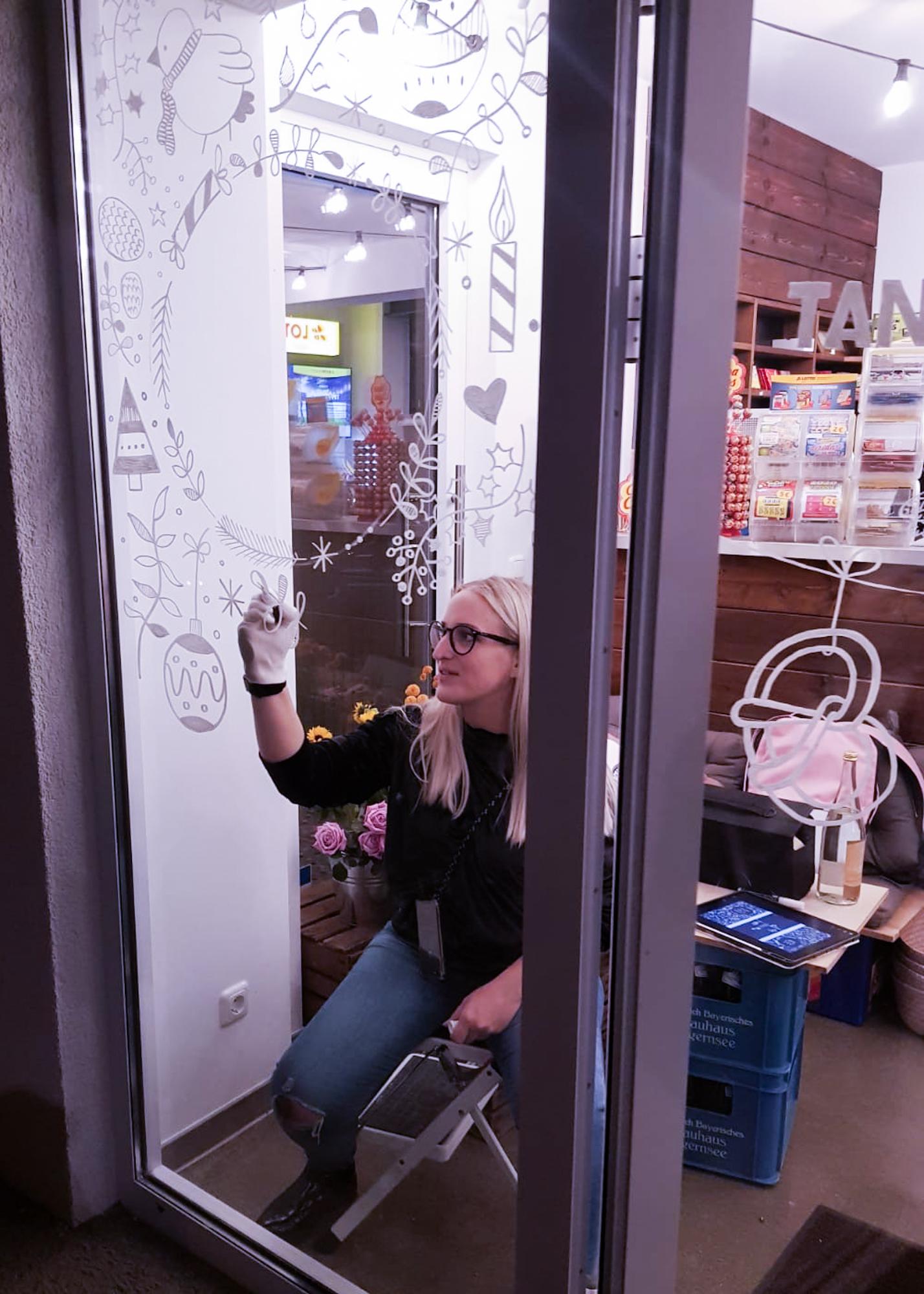 Lena malt das Schaufenster der Superkiosks Tante Ohm mit Markerstiften an.