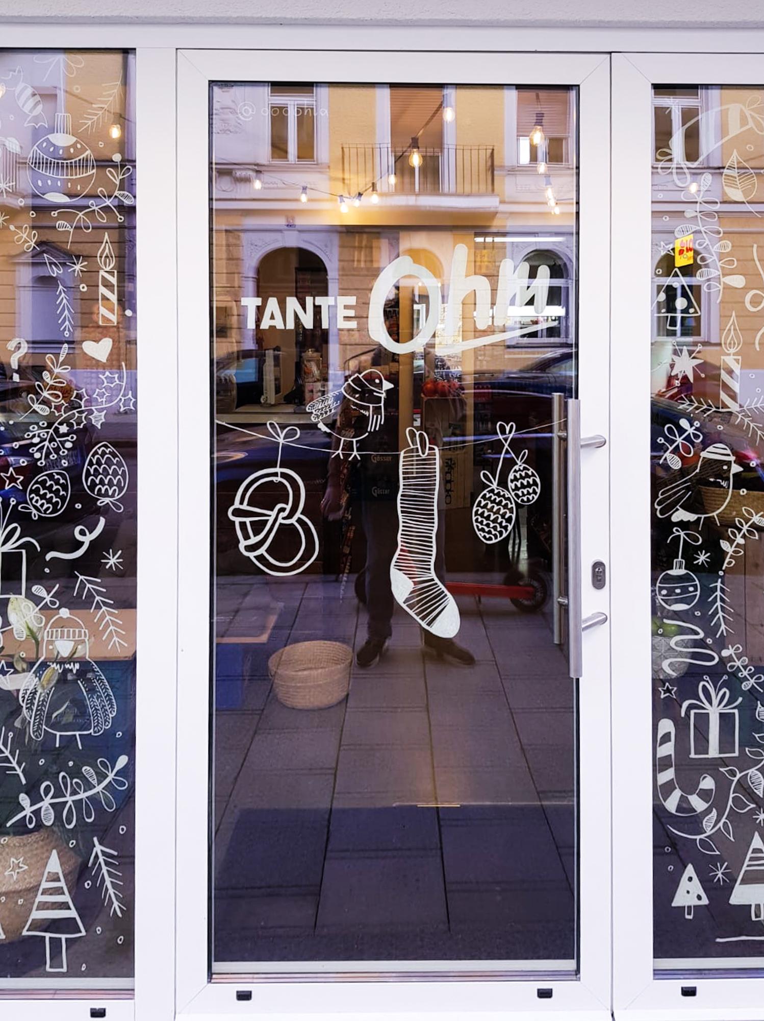 Foto von der Ladenfront des Kiosks mit der Fensterbemalung auf der Tür im Fokus.