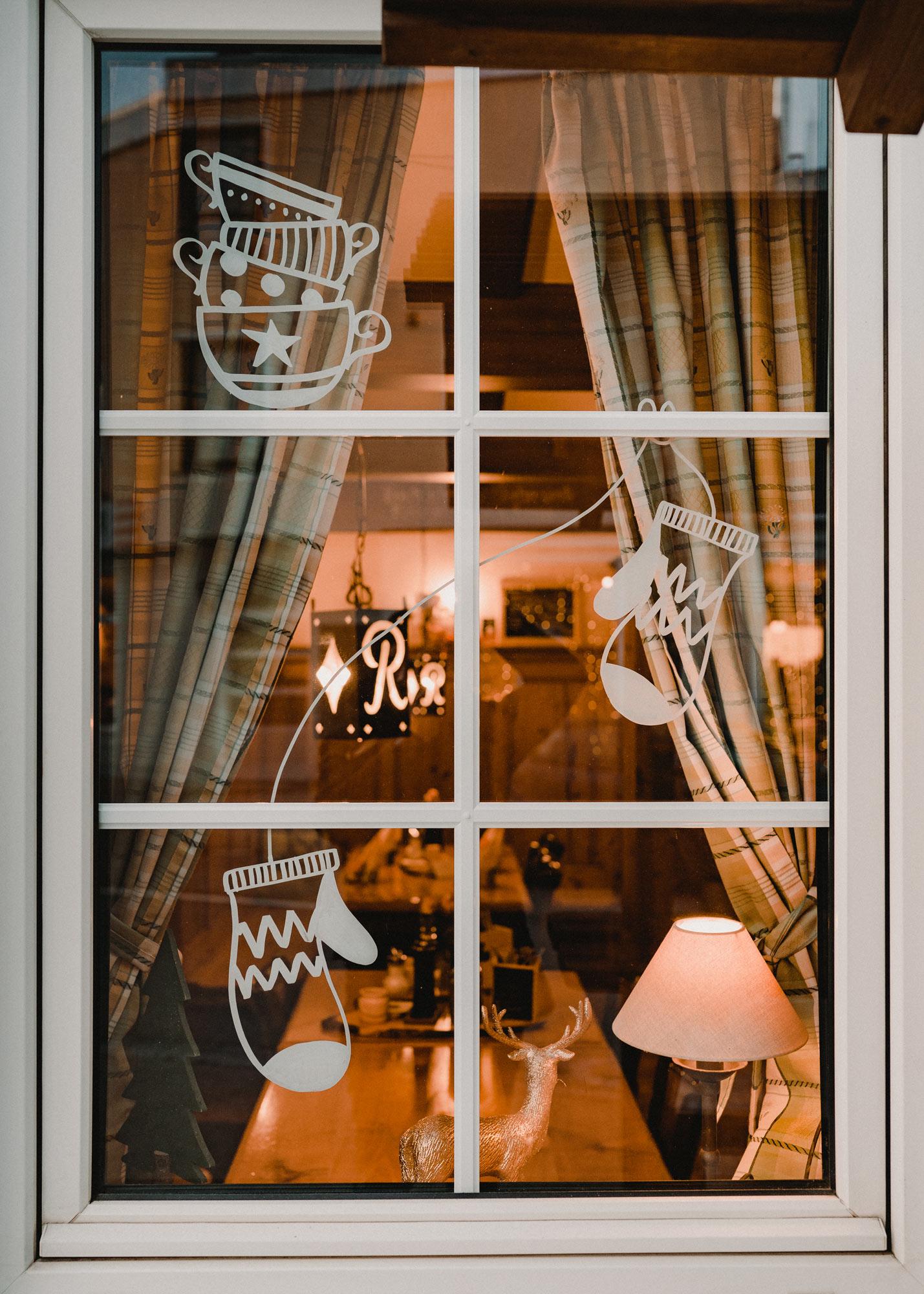 Gasthausfenster mit weißer Bemalung: Ein Stapel Tassen, und ein paar Kinderhandschuhe, die an einer Schnur hängen.