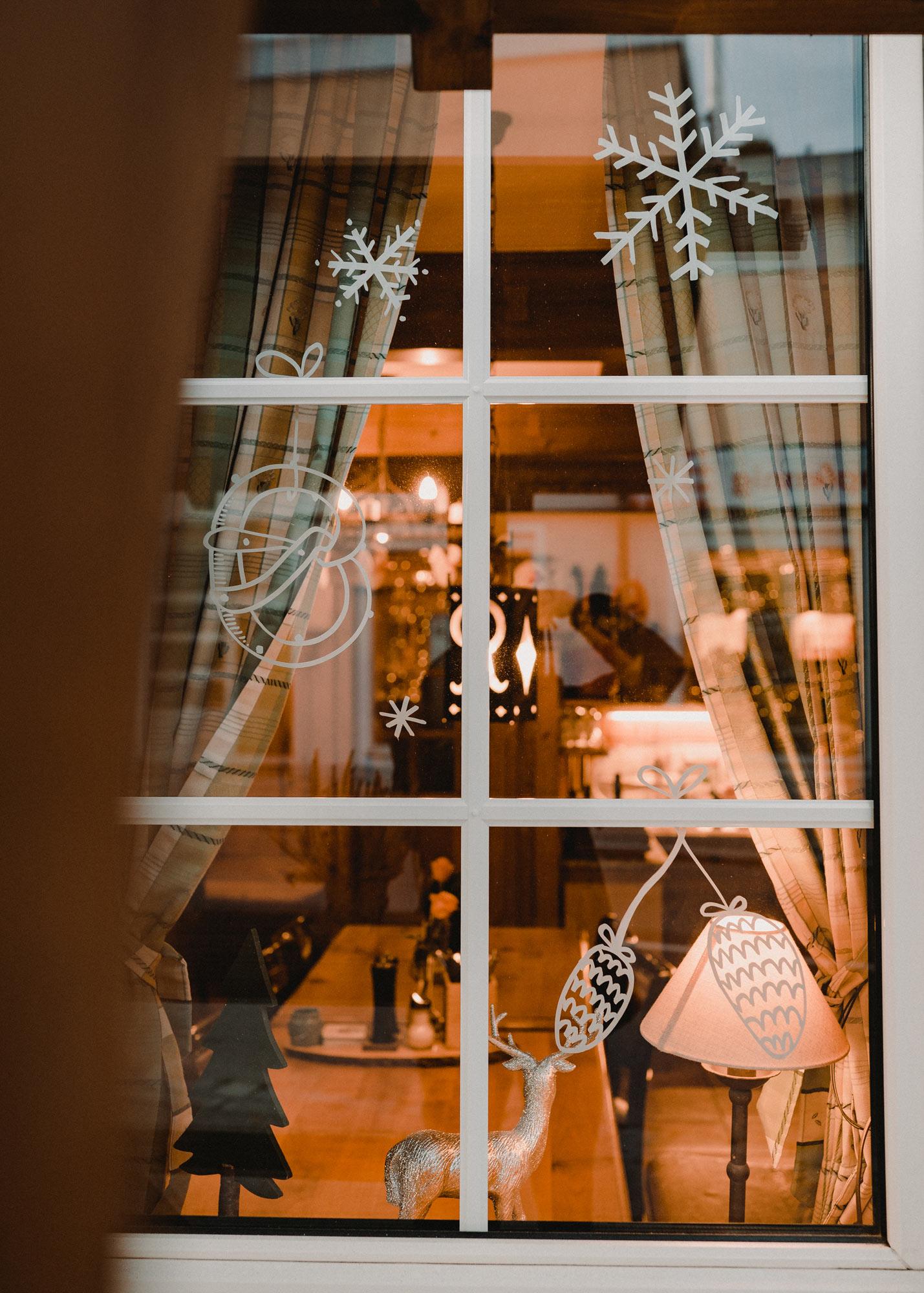 Gasthausfenster mit weißer Bemalung: Schneeflocken, Eine Breze und Tannenzapfen.
