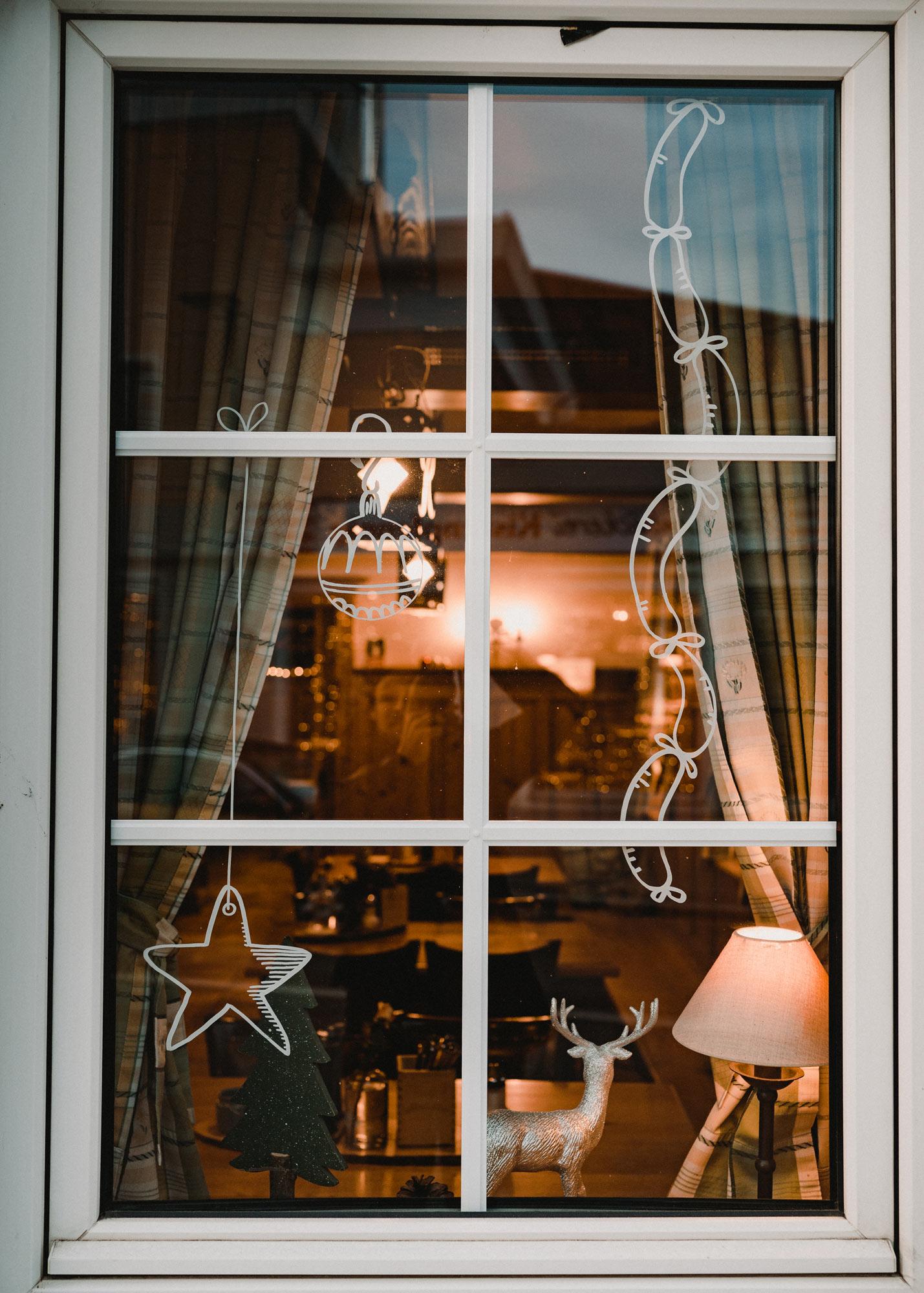 Gasthausfenster mit weißer Bemalung: Ein Stern an einer Schnur, eine Christbaumkugel und viele Würste hängen von oben herab.