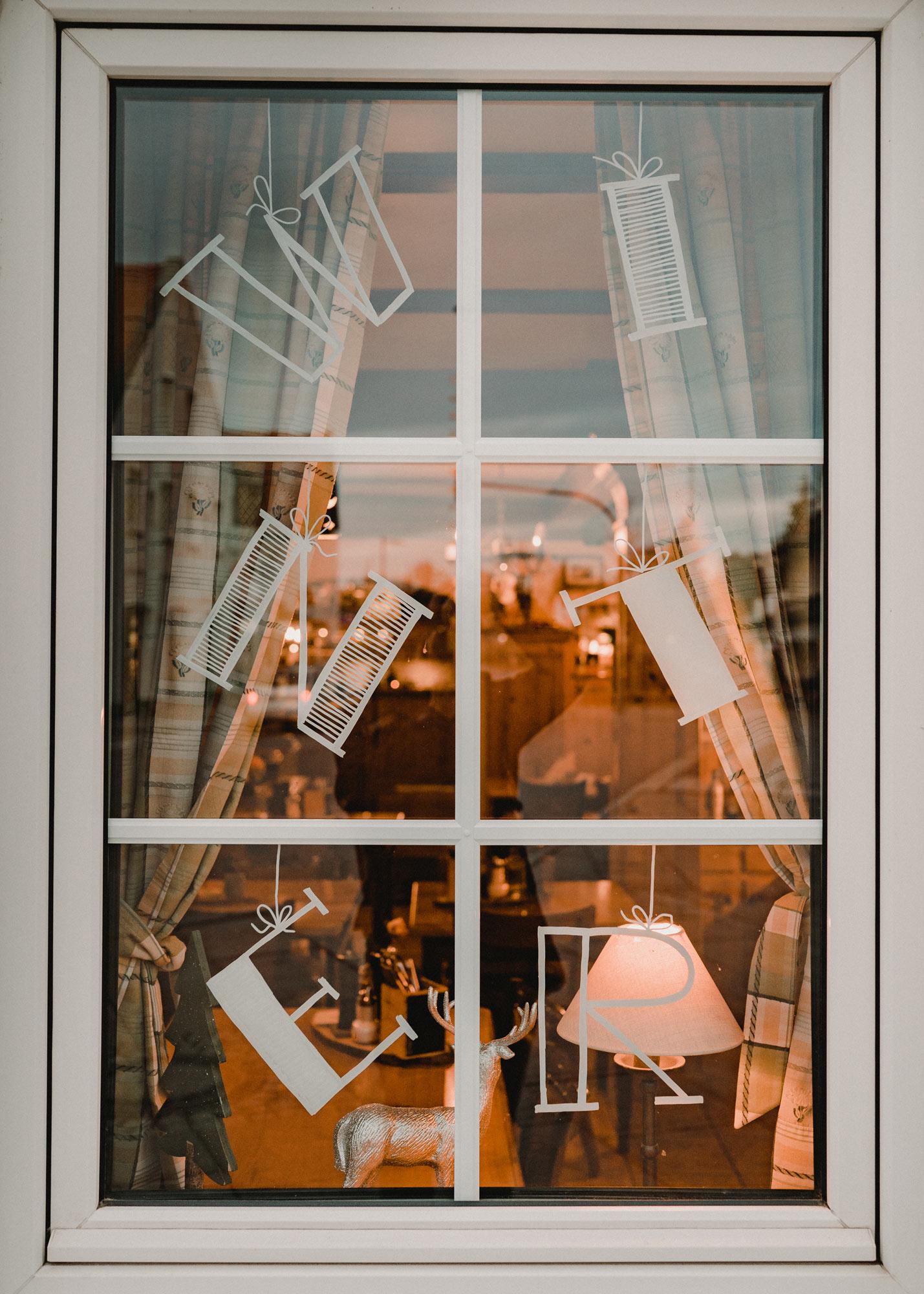 Gasthausfenster mit weißer Bemalung: Die Buchstaben W I N T E R sind auf dem unterteilten Fenster zu sehen.