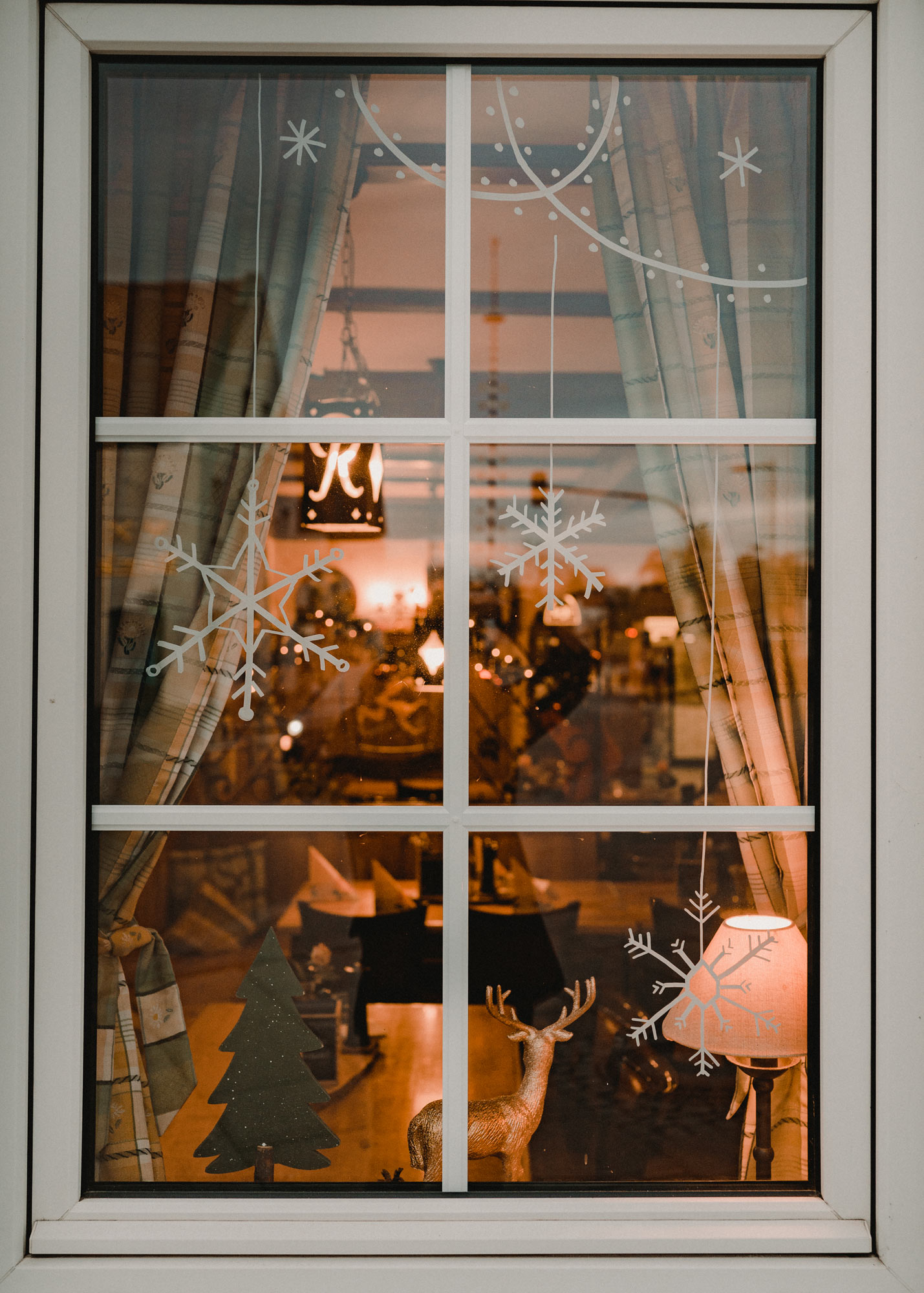 Gasthausfenster mit weißer Bemalung: Lichtergirlanden und Schneeflocken.