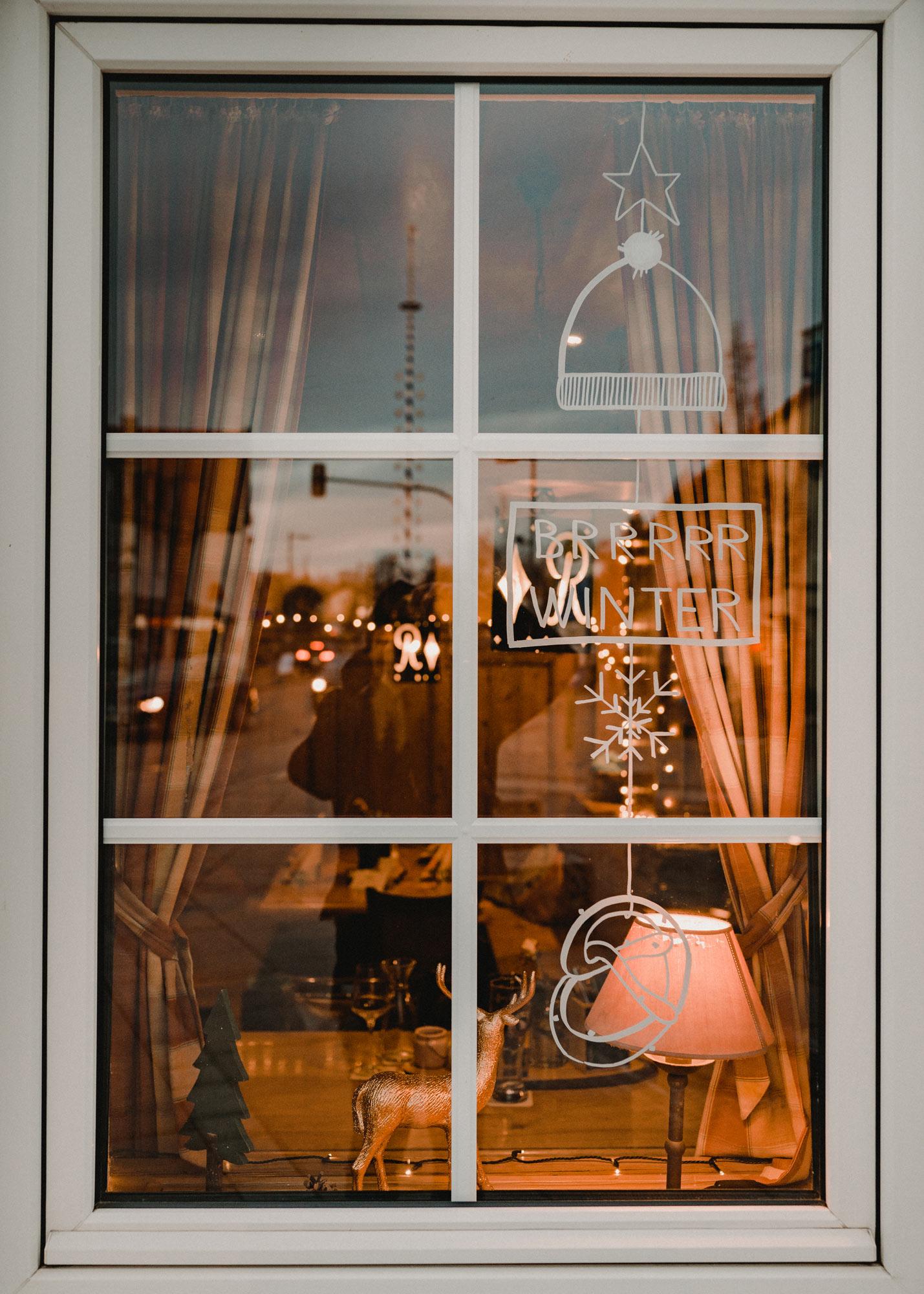 Gasthausfenster mit weißer Bemalung: Ein Mobile bestehend aus einem Stern, Mütze, Schild, Schneeflocke und Breze.