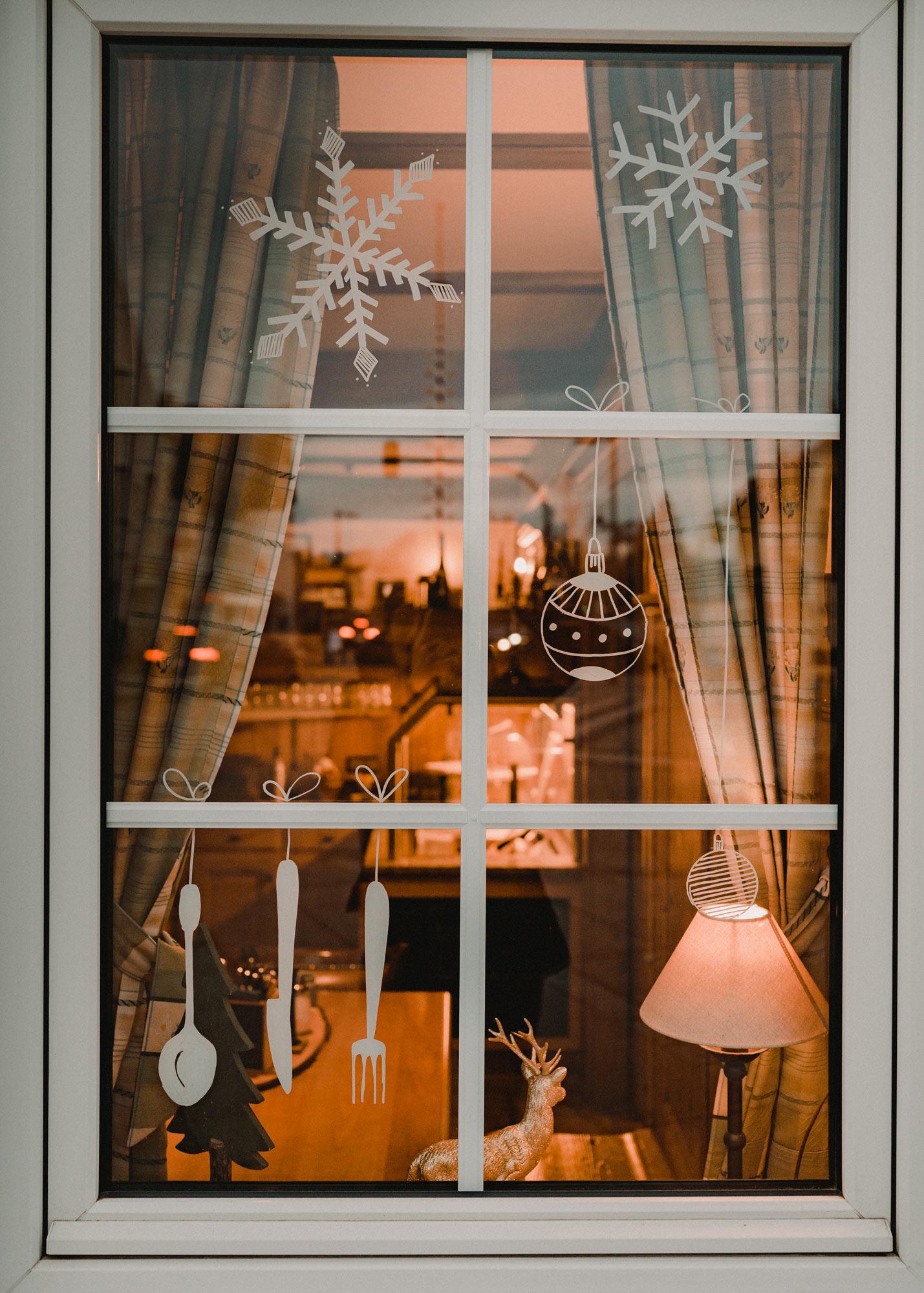 Gasthausfenster mit weißer Bemalung: Besteck, Schneeflocken und Christbaumkugeln.