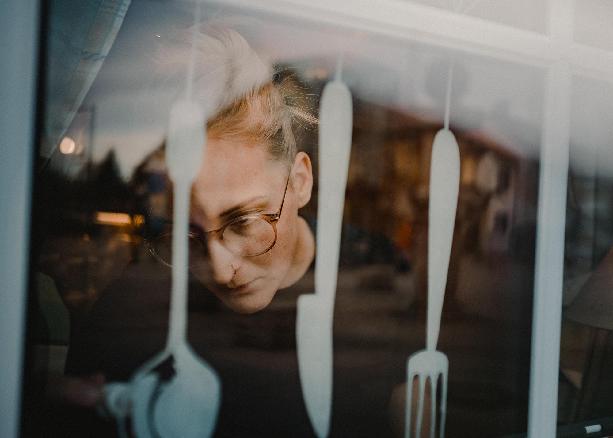 Lena malt Besteck mit Markerstifen an die Fensterscheibe.