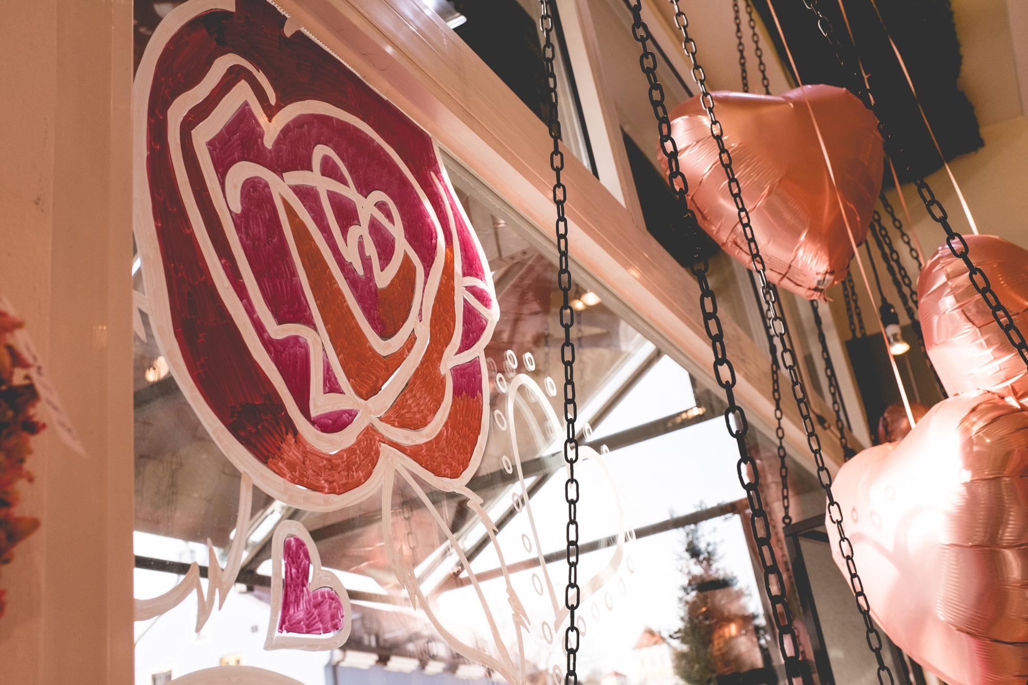 Eine auf das Schaufenster gezeichnete Rose in pink