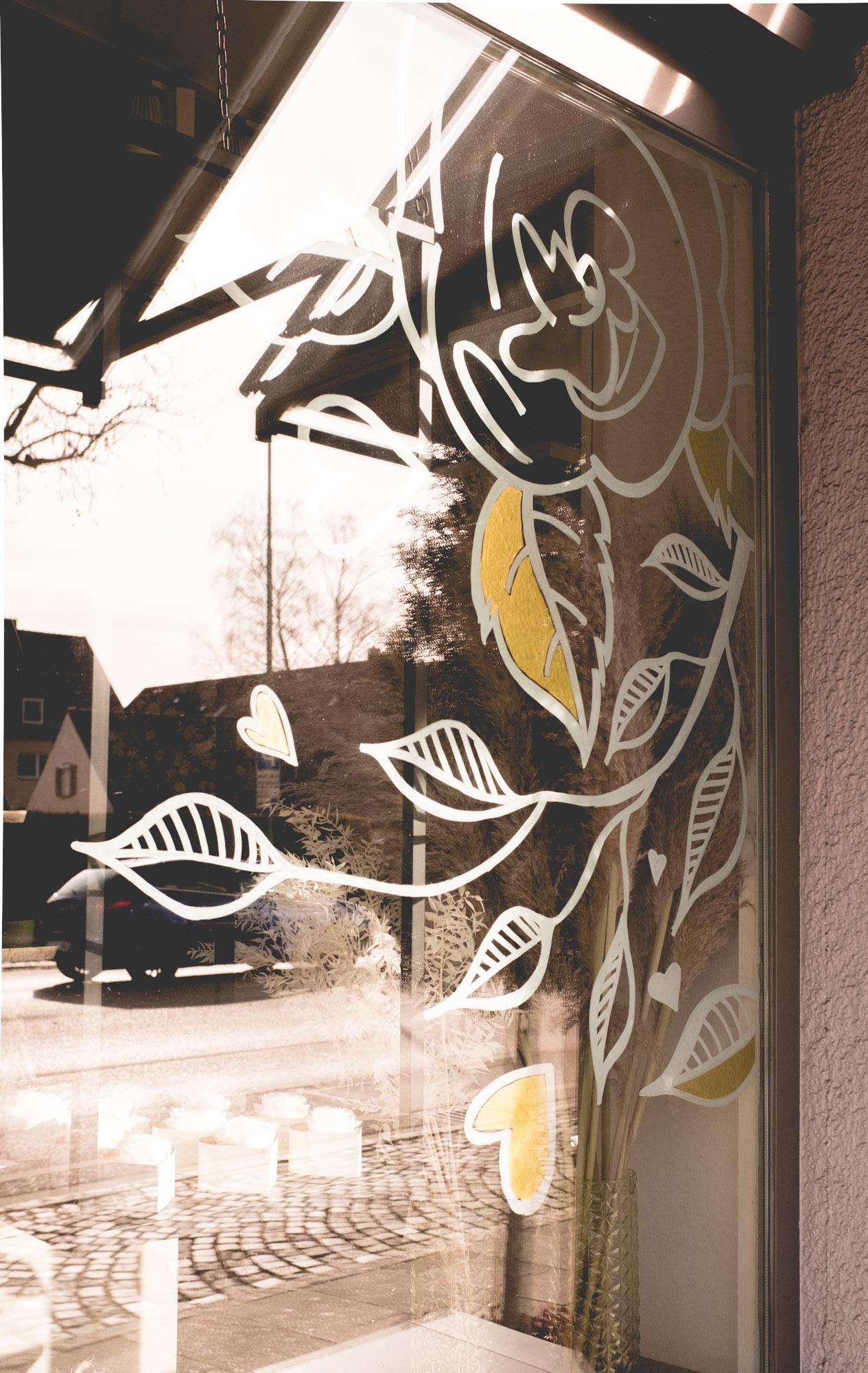 Eine auf das Schaufenster gezeichnete Rose mit Blättern und Herzen