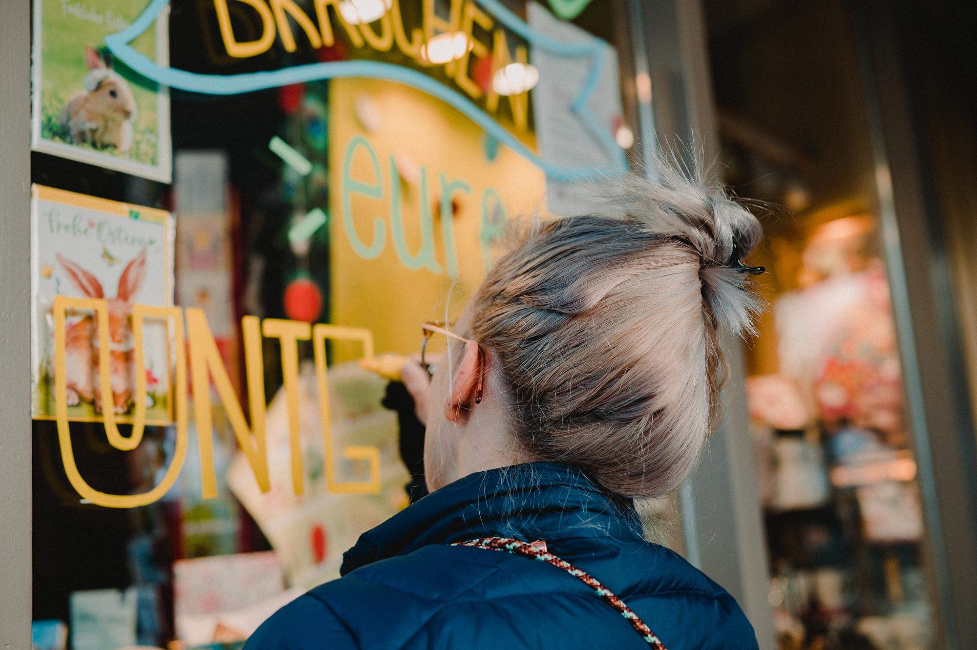 EIne Frau bemalt eine Schaufensterscheibe mit einem Marker.