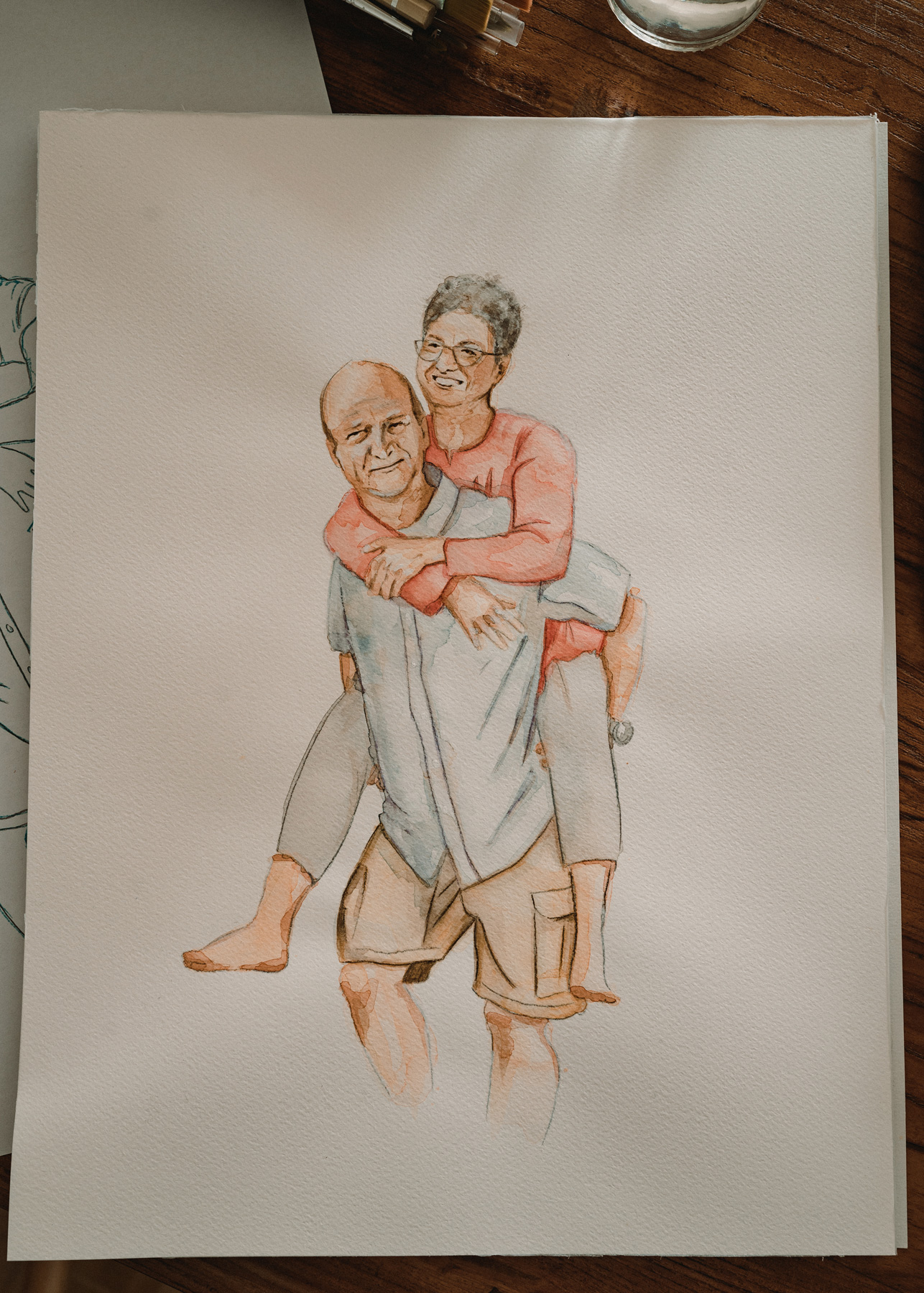 Das Porträt zeigt ein Paar. Der Mann trägt die Frau Huckepack.