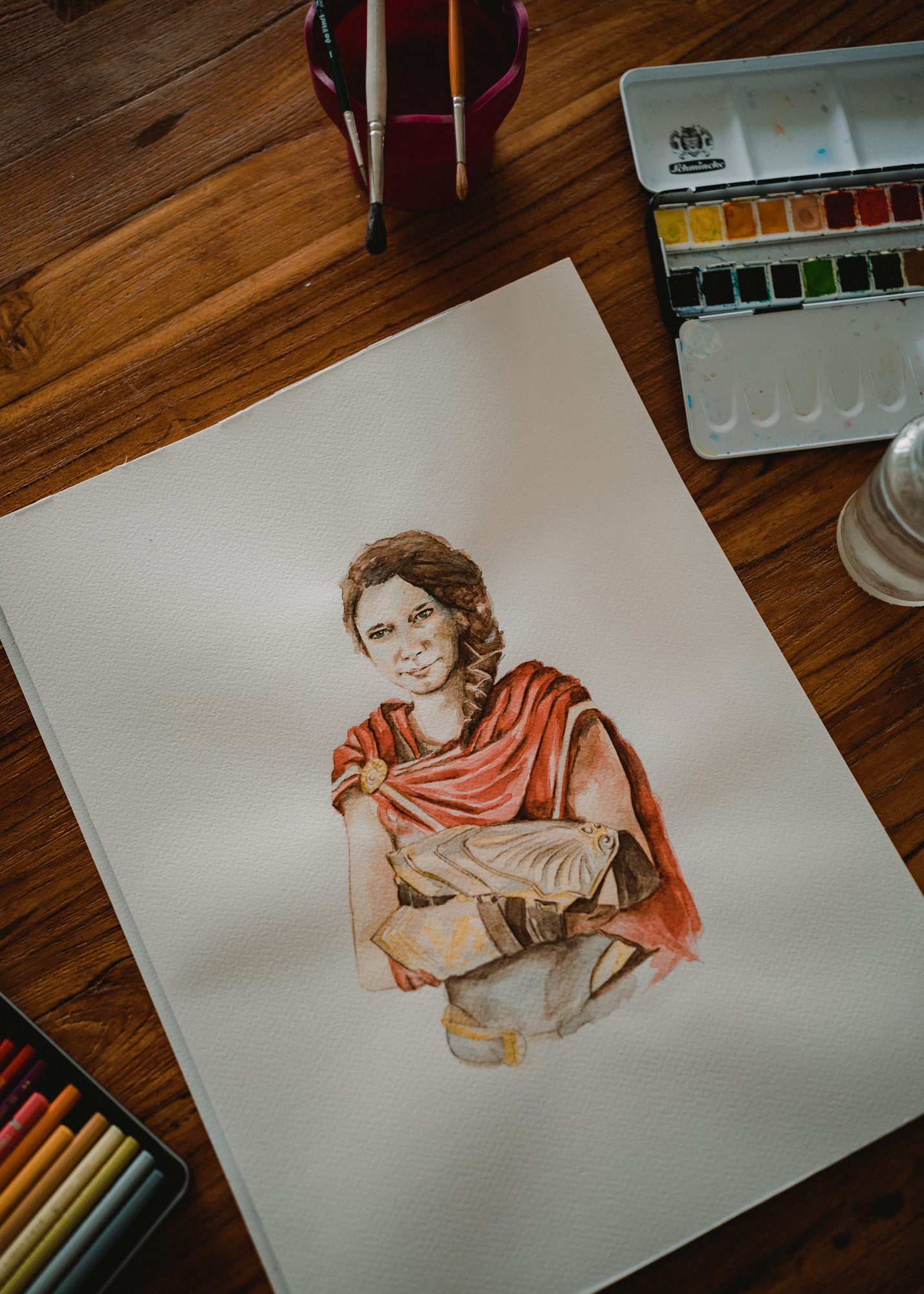 Das Foto zeigt ein Aquarell-Porträt einer jungen Frau im Kostüm der griechischen Heldin aus dem Computerspiel