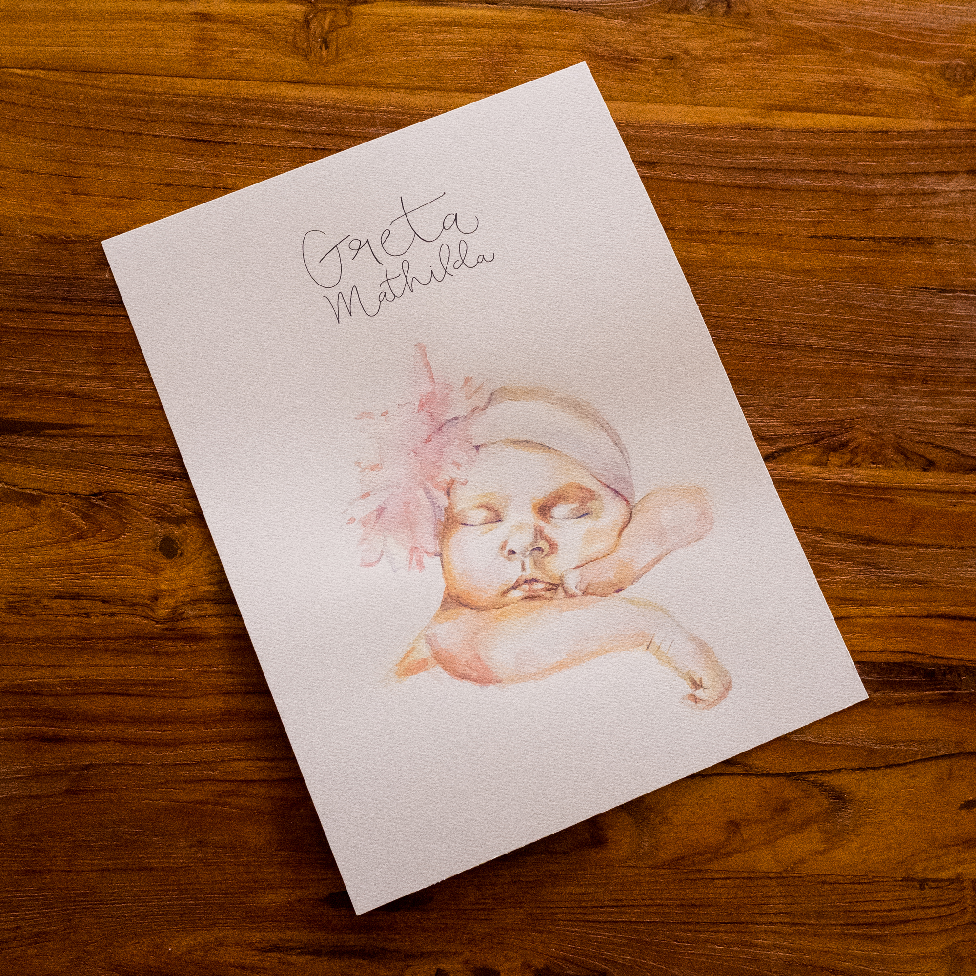 Ein Babyporträt mi Aquarelltechnik gemalt und dem Namen in Handschrift.