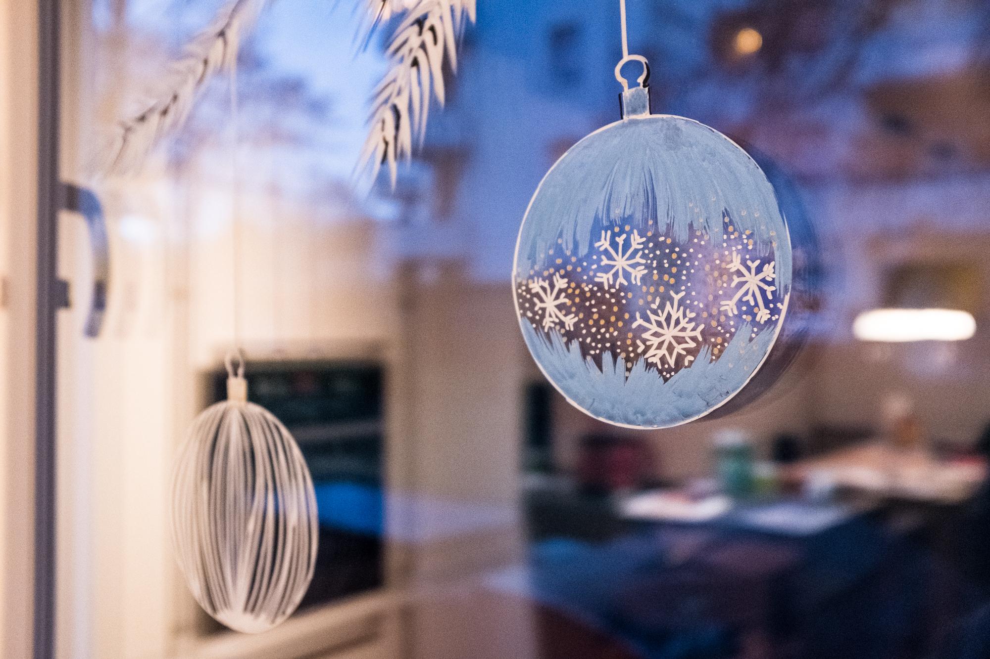 Ein mit Acrylmarkern bemaltes Fenster zeigt Weihnachtskugeln an einem Zweig hängend.