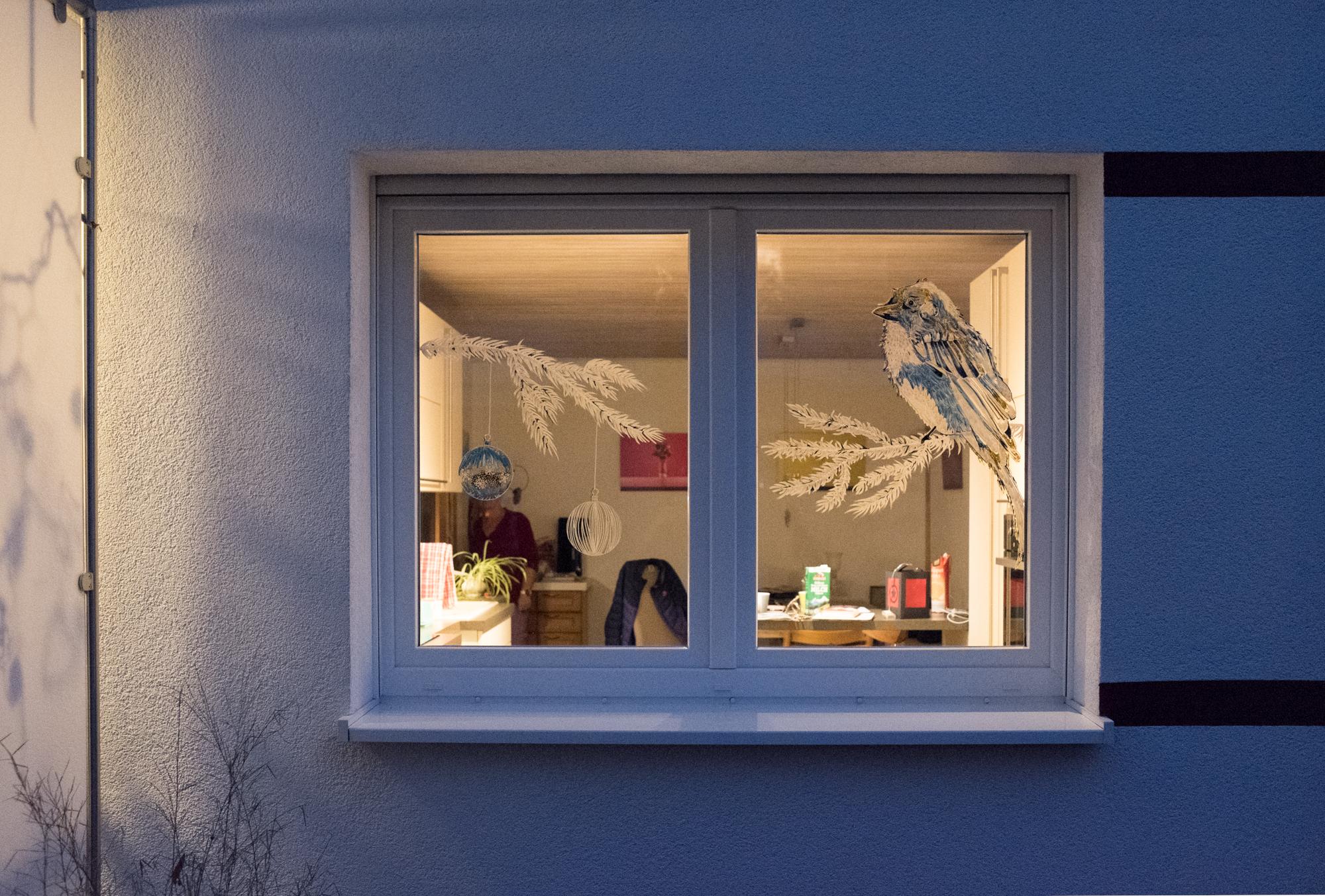 Ein mit Acrylmarkern bemaltes Fenster zeigt einen Vogel auf einem Zweig sitzend.
